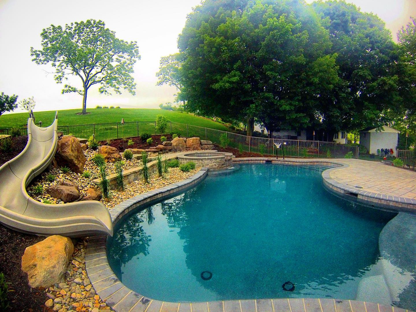 pool with sliding board and hot tub
