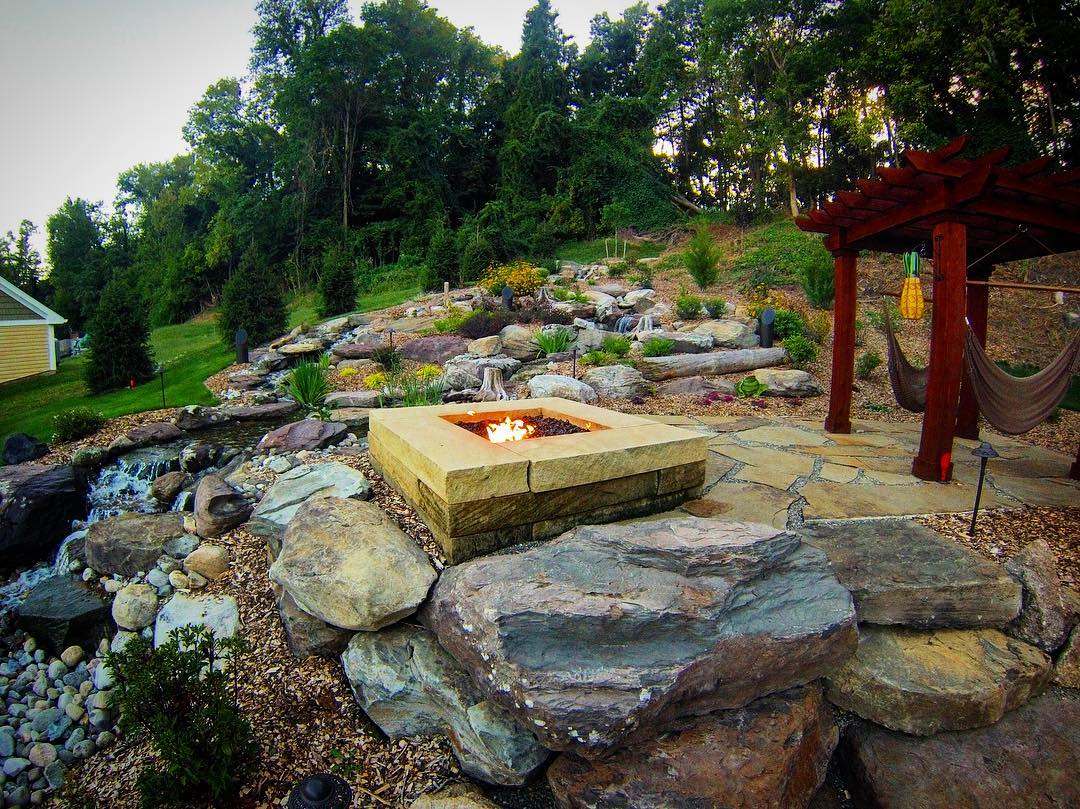 Natural stone patio with gas fire pit and pergola